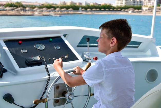 Adolescente ao leme controla um iate no mar.