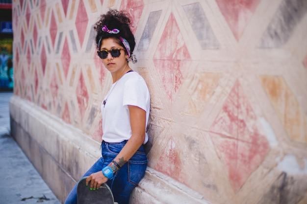 Adolescente apoiada no muro de concreto