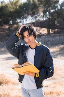 Adolescente asiática, coçando a cabeça e lendo o livro no parque