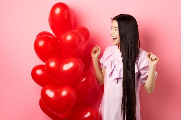 Adolescente asiática com cabelo comprido, torcendo por um presente romântico de dia dos namorados, olhando para o logotipo e sorrindo feliz, pulando de alegria perto de balões de coração de presente de amantes, fundo rosa.