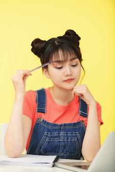 Adolescente asiática fazendo lição de casa