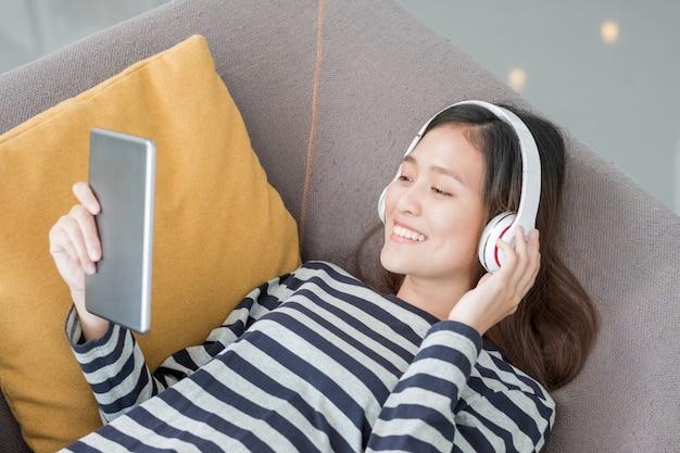 Adolescente asiática, menina, desgaste, fone de ouvido, ouvindo, música, jogo, tablet, computador, coloque, sofá