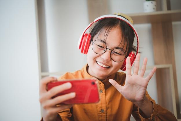 Adolescente asiático em vestido amarelo falando em um smartphone de videochamada durante a epidemia de coronavírus covid-19