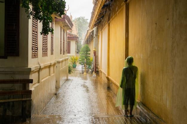 Adolescente asiático esperando a chuva de monção parar.
