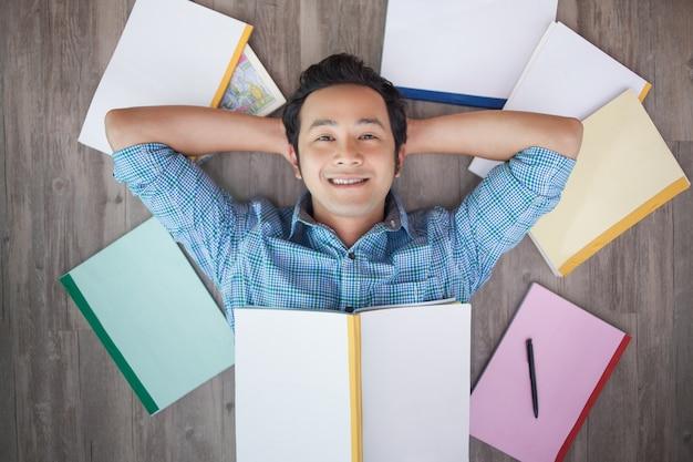 Adolescente asiático feliz deitado no assoalho entre livros