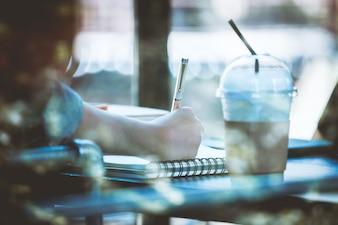 Adolescente asiático senta sozinho em um café com caderno