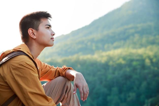 Adolescente asiático sentado na borda da ponte do penhasco e olhando para a montanha.