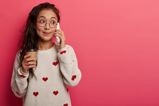 Adolescente asiático surpreso e atraente fala no celular, ouve boatos, bebe café para viagem e tem rabo de cavalo comprido