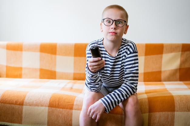 Adolescente assistindo tv com óculos usando o controle remoto enquanto está sentado no sofá na sala de estar em casa em