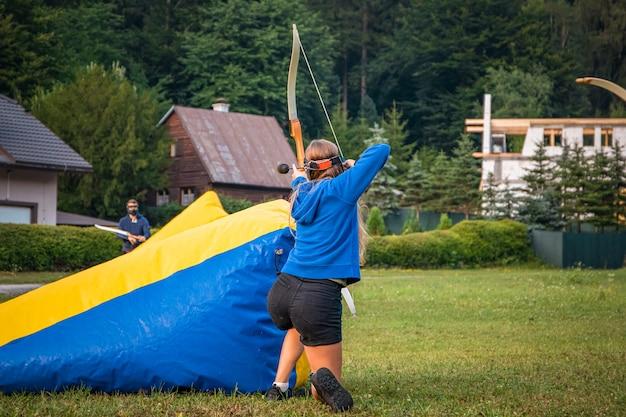 Adolescente atacando o time adversário com arco e flecha