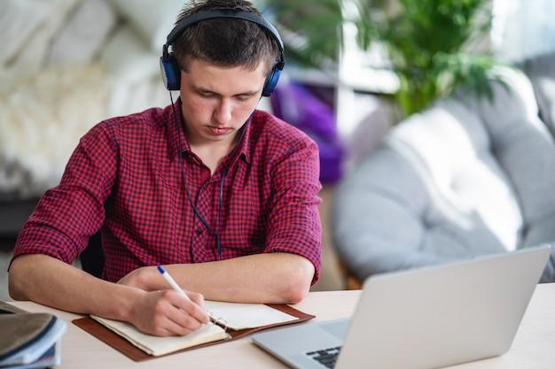 Adolescente ativo com fones de ouvido ouve palestras, faz no caderno, usando laptop