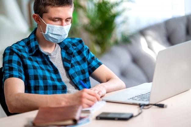 Adolescente ativo em uma máscara com laptop durante quarentena de coronavírus