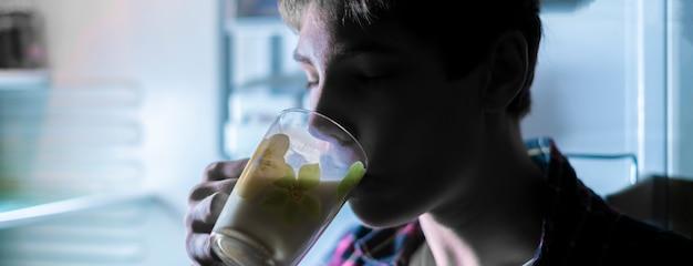 Adolescente atraente beber leite fresco da geladeira durante a noite