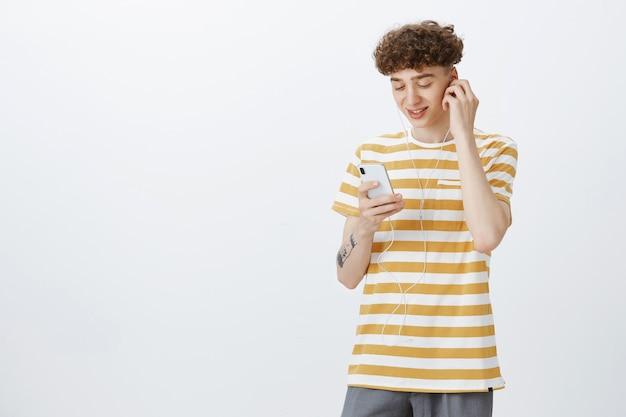 Adolescente atraente posando contra a parede branca