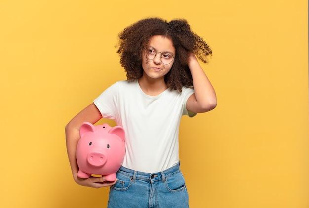 Adolescente bastante afro, apontando para a câmera com um sorriso satisfeito, confiante e amigável, escolhendo você. conceito de economia