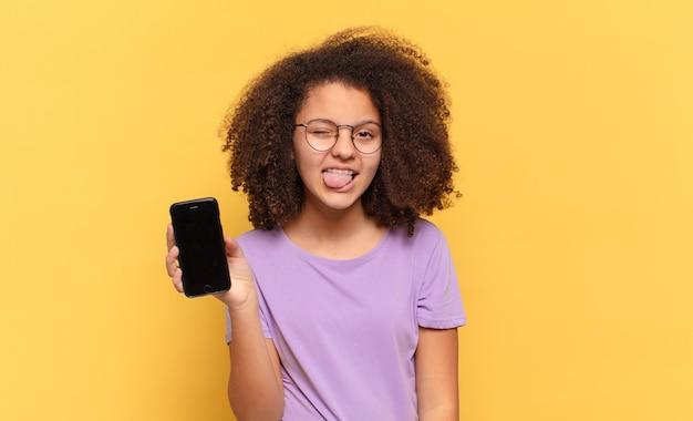 Adolescente bastante afro com atitude alegre, despreocupada e rebelde, brincando e mostrando a língua, se divertindo e segurando um celular