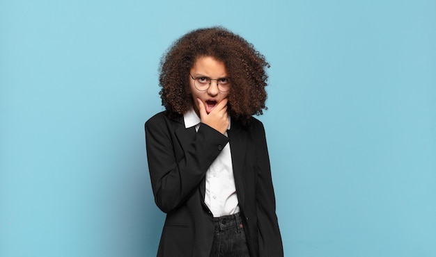 Adolescente bastante afro com boca e olhos bem abertos e mão no queixo, sentindo-se desagradavelmente chocada, dizendo o quê ou uau. conceito de negócio humorístico