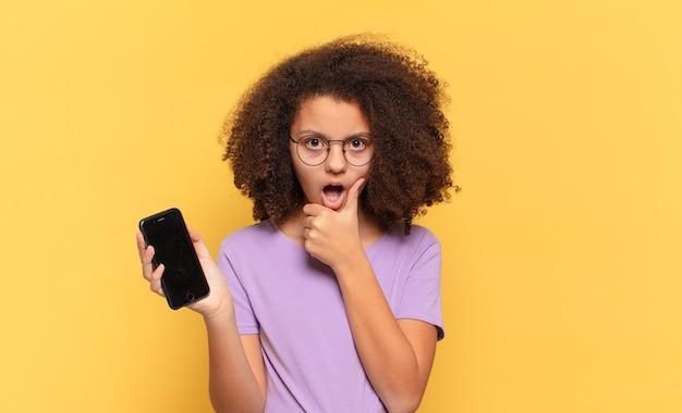 Adolescente bastante afro com boca e olhos bem abertos e mão no queixo, sentindo-se desagradavelmente chocado, dizendo o quê ou uau e segurando um celular
