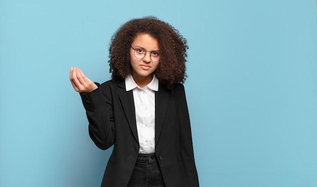 Adolescente bastante afro fazendo capice ou gesto de dinheiro, dizendo para você pagar suas dívidas !. conceito de negócio humorístico