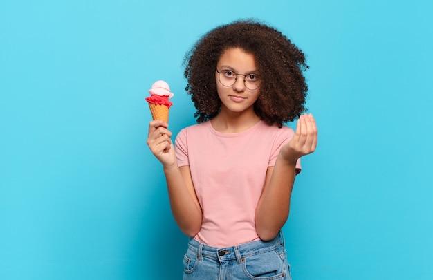 Adolescente bastante afro fazendo capice ou gesto de dinheiro, dizendo para você pagar suas dívidas !. conceito de sorvete de sumer