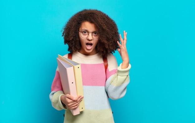 Adolescente bastante afro, gritando com as mãos no ar, sentindo-se furioso, frustrado, estressado e chateado. conceito de estudante