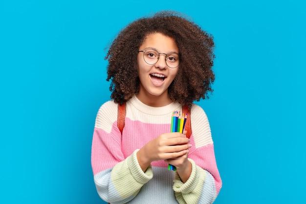 Adolescente bastante afro parecendo feliz e agradavelmente surpreso, animado com uma expressão de fascínio e choque. conceito de estudante