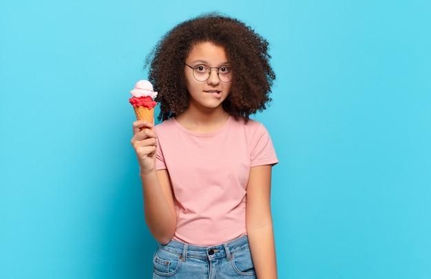 Adolescente bastante afro parecendo perplexo e confuso, mordendo o lábio com um gesto nervoso, sem saber a resposta para o problema. conceito de sorvete de sumer