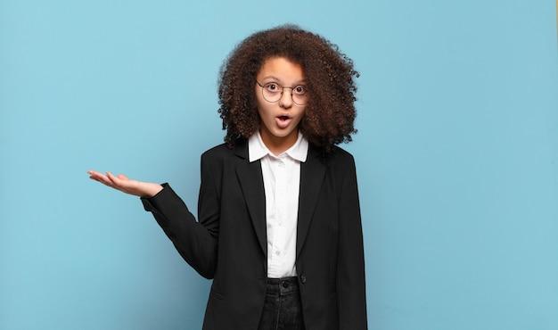 Adolescente bastante afro parecendo surpreso e chocado, com o queixo caído segurando um objeto com a mão aberta na lateral. conceito de negócio humorístico