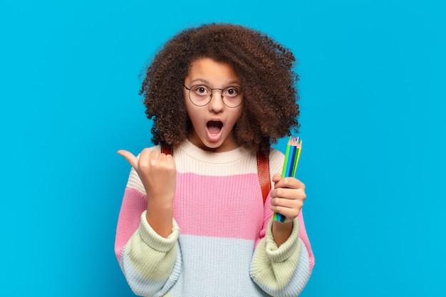 Adolescente bastante afro parecendo surpreso em descrença, apontando para um objeto ao lado e dizendo uau, inacreditável. conceito de estudante