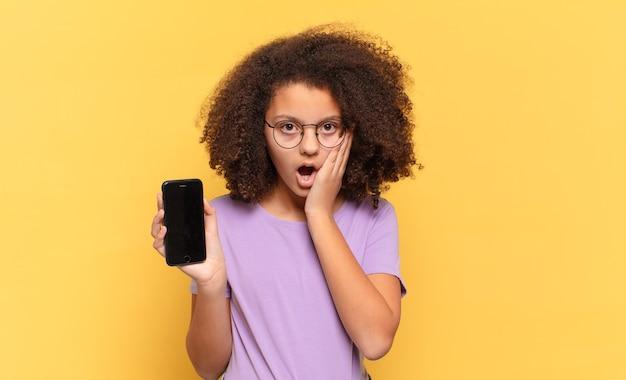 Adolescente bastante afro se sentindo chocado e assustado, parecendo apavorado com a boca aberta, as mãos nas bochechas e segurando um celular