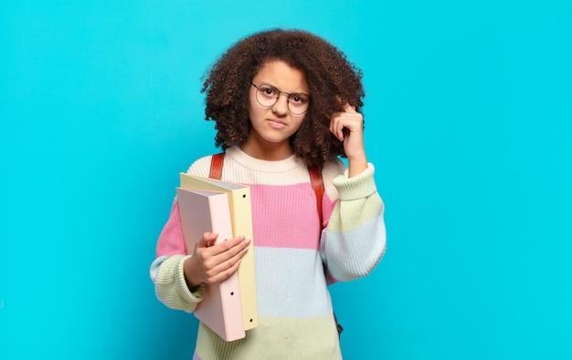 Adolescente bastante afro se sentindo confuso e perplexo, mostrando que você é louco, louco ou maluco. conceito de estudante