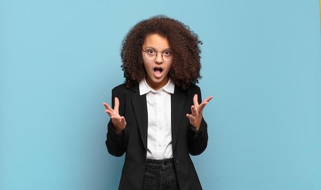 Adolescente bastante afro se sentindo extremamente chocado e surpreso, ansioso e em pânico