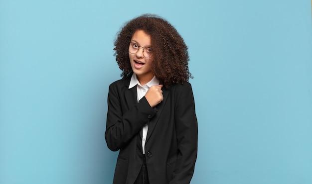 Adolescente bastante afro se sentindo feliz, positivo e bem-sucedido