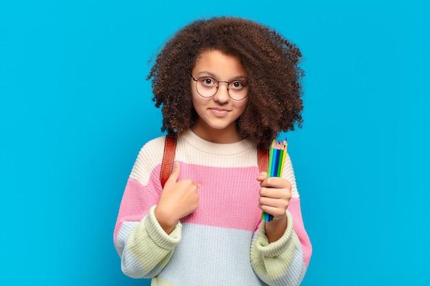 Adolescente bastante afro se sentindo feliz, surpreso e orgulhoso, apontando para si mesmo com um olhar animado e surpreso.