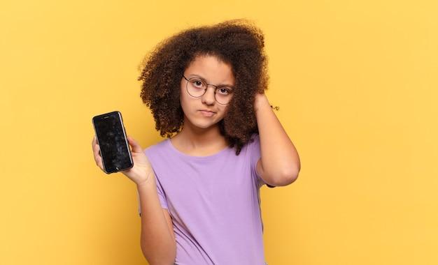 Adolescente bastante afro se sentindo perplexo e confuso, coçando a cabeça e olhando para o lado segurando um celular