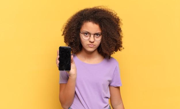 Adolescente bastante afro se sentindo triste, chateado ou com raiva e olhando para o lado com uma atitude negativa, franzindo a testa em desacordo e segurando uma cela