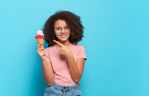 Adolescente bastante afro sorrindo alegremente, sentindo-se feliz e apontando para o lado e para cima, mostrando o objeto no espaço da cópia