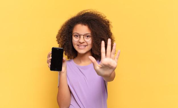 Adolescente bastante afro sorrindo e parecendo amigável, mostrando o número cinco ou quinto com a mão para a frente, contando e segurando um celular