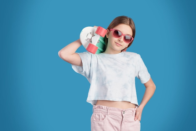 Adolescente bastante relaxado usando óculos escuros, camiseta branca e jeans segurando o skate no ombro e em frente à câmera