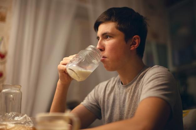 Adolescente bebe leite na cozinha à noite antes de ir para a cama