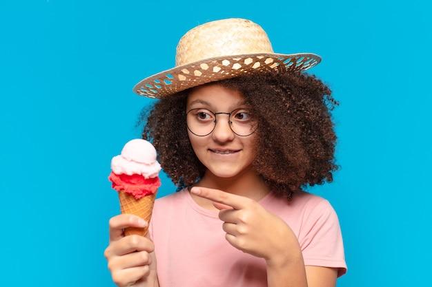 Adolescente bonita afro com chapéu e tomando um sorvete