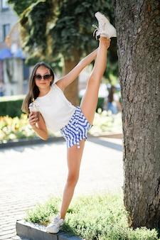 Adolescente bonita bebe uma bebida fresca no calor do verão e se diverte. férias de verão engraçadas