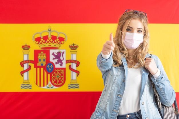 Adolescente bonita mostra o polegar em pé na frente da bandeira espanhola.