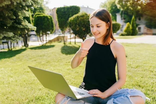 Adolescente bonito bonito, aparecendo um polegar ao ter uma conversa por vídeo com os amigos, sentado na grama, no parque, ao ar livre. vestida com roupas elegantes.