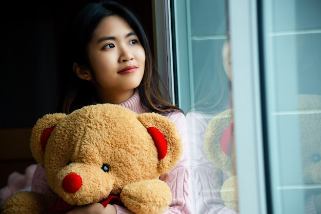Adolescente bonito com grande urso de pelúcia