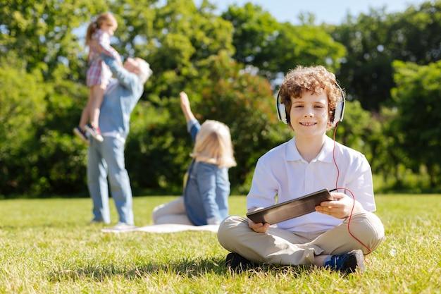 Adolescente bonito com um sorriso no rosto, usando fones de ouvido e segurando o tablet com as duas mãos