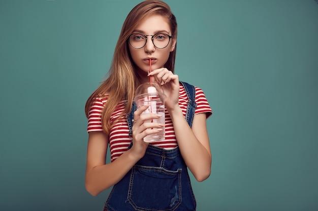 Adolescente bonito de macacão jeans e óculos com água com gás