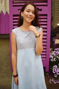 Adolescente bonito na blusa azul, contra a janela de madeira violeta com flores.