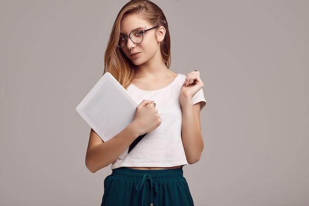 Adolescente bonito na camisa branca e óculos, segurando o tablet digital