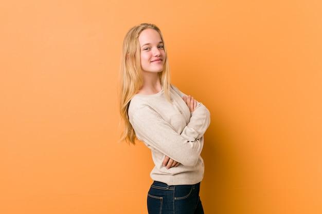 Adolescente bonito posando em pé contra uma laranja